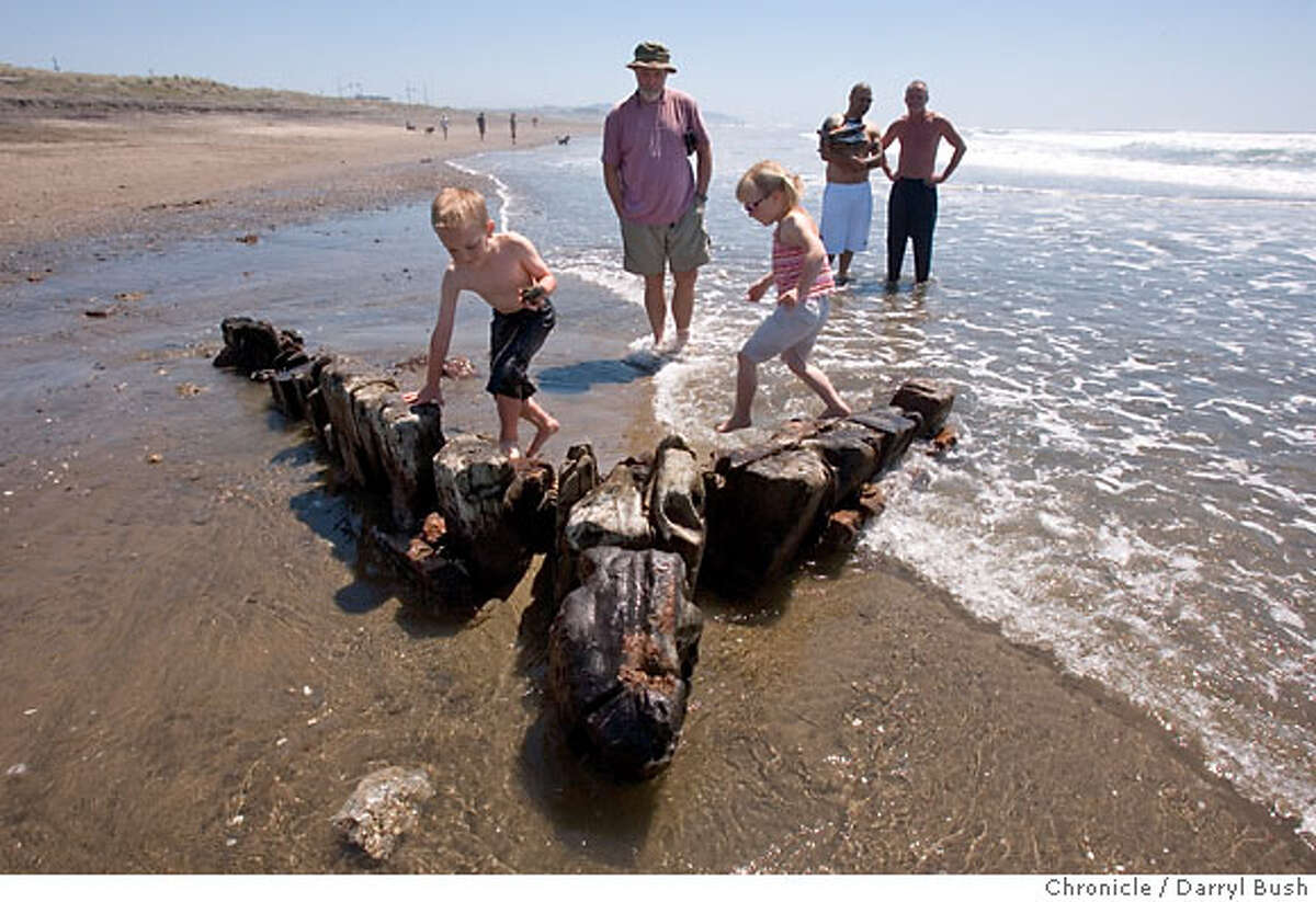 Bystanders including Brendan Earley, center, watch as Megan Van Koll, 6, and Mark Walseman, 6, both from San Francisco play as they walk on top of a portion of a wrecked 19th century clipper ship that has recently surfaced on Ocean Beach in San Francisco, CA, on Tuesday, May, 8, 2007. photo taken: 5/8/07 Darryl Bush / The Chronicle ** Megan Van Koll, Mark Walseman (with mother of Megan: Theona Van Koll not shown), Brendan Earley (cq)