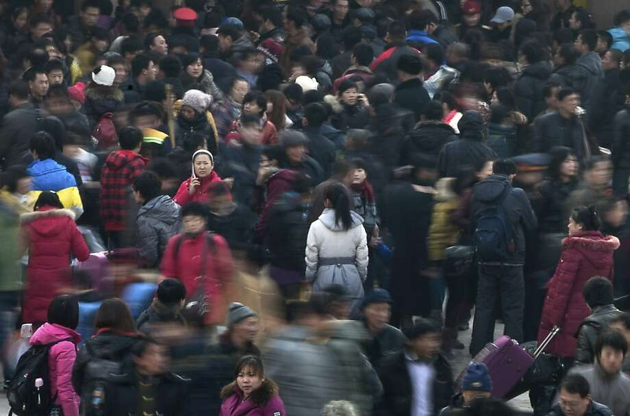 FILE - In this Jan. 8, 2012 file photo, people rush to catch their train at Beijing station in Beijing, China as millions of Chinese are expected to cramp onto China's train network in the coming weeks to return home for the Chinese lunar new year that starts on Jan. 23, 2012. Beijing says more Chinese are living in cities than in the countryside for the first time in the nation's history. The National Bureau of Statistics said Tuesday, Jan. 17, that urban dwellers accounted for 51.27 percent of China's 1.34 billion people at the end of last year. (AP Photo/Andy Wong, File) Photo: Andy Wong, Associated Press