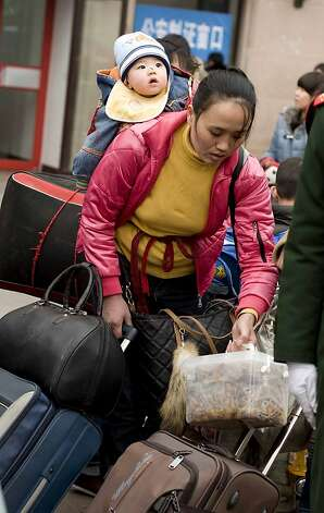 Chinese passengers prepare to board their trains at a railway station in Beijing on January 16, 2011 as they return home for the lunar Chinese New Year holidays which this year marks the year of the dragon on January 23.  China said the number of people living in cities exceeded the rural population for the first time with urban dwellers now representing 51.27 percent of China's entire population of nearly 1.35 billion, a development experts warned was likely to put strain on society and the environment.  CHINA OUT AFP PHOTO (Photo credit should read STR/AFP/Getty Images) Photo: Str, AFP/Getty Images