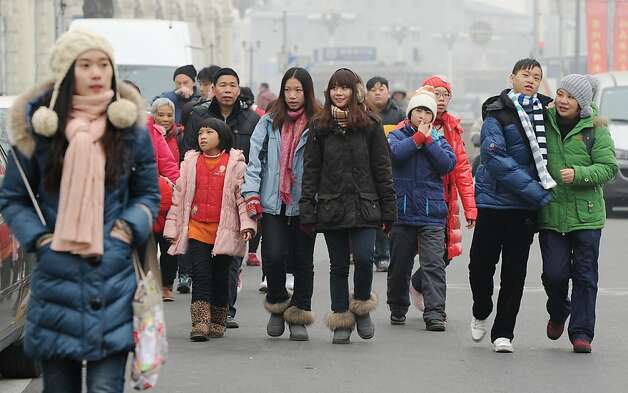 Domestic Chinese tourists view the sights near Tiananmen Square at the start of the Chinese New Year holiday in Beijing on January 17 2012.  China said the number of people living in cities exceeded the rural population for the first time and the shift marks a turning point for China, which for centuries has been a mainly agrarian nation, but which has witnessed a huge population shift to cities. Urban dwellers now represent 51.27 percent of China's entire population of nearly 1.35 billion -- or 690.8 million people -- the National Bureau of Statistics (NBS) said.        AFP PHOTO/Mark RALSTON (Photo credit should read MARK RALSTON/AFP/Getty Images) Photo: Mark Ralston, AFP/Getty Images