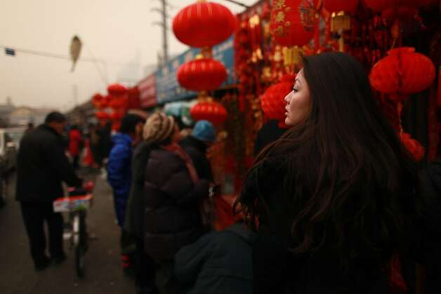A woman shops at a market in a largely migrant populated area of Beijing on January 17, 2012.  China said the number of people living in cities exceeded the rural population for the first time, a historic shift  that experts said would put a strain on society and the environment. AFP PHOTO / Ed Jones (Photo credit should read Ed Jones/AFP/Getty Images) Photo: Ed Jones, AFP/Getty Images