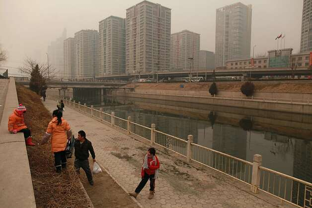 A family climbs down the bank of a canal before high-rise apartments in Beijing on January 17, 2012.  China said the number of people living in cities exceeded the rural population for the first time, a historic shift that experts said would put a strain on society and the environment. AFP PHOTO / Ed Jones (Photo credit should read Ed Jones/AFP/Getty Images) Photo: Ed Jones, AFP/Getty Images