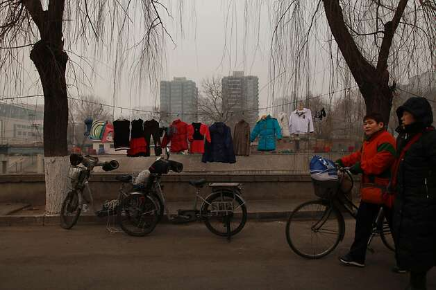 Clothes dry on a line before high-rise apartments in a shanty area of Beijing on January 17, 2012. China said the number of people living in cities exceeded the rural population for the first time, a historic shift  that experts said would put a strain on society and the environment. AFP PHOTO / Ed Jones (Photo credit should read Ed Jones/AFP/Getty Images) Photo: Ed Jones, AFP/Getty Images