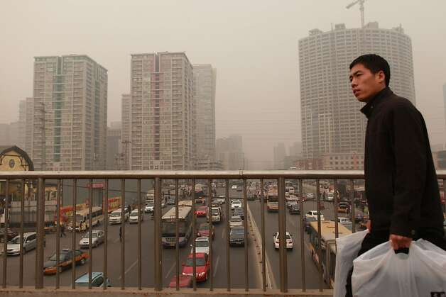 A man walks over a road bridge before high-rise apartments in Beijing on January 17, 2012. China said the number of people living in cities exceeded the rural population for the first time, a historic shift  that experts said would put a strain on society and the environment. AFP PHOTO / Ed Jones (Photo credit should read Ed Jones/AFP/Getty Images) Photo: Ed Jones, AFP/Getty Images