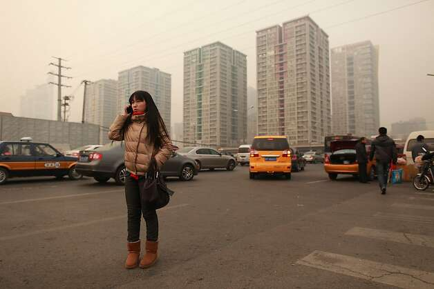A woman talks on a mobile phone as she stands on a roadside before high-rise apartments in Beijing on January 17, 2012. China said the number of people living in cities exceeded the rural population for the first time, a historic shift  that experts said would put a strain on society and the environment. AFP PHOTO / Ed Jones (Photo credit should read Ed Jones/AFP/Getty Images) Photo: Ed Jones, AFP/Getty Images