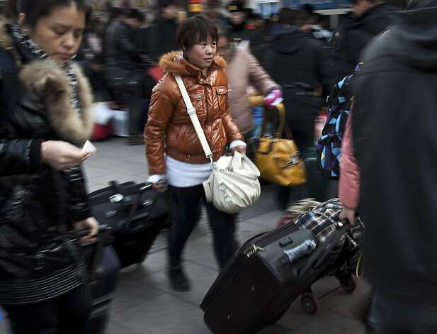 FILE - In this Jan. 8, 2012 file photo, people carry luggage to catch their train upon arrival at Beijing station as millions of Chinese are expected to cramp onto China's train network in the coming weeks to return home for the Chinese lunar new year that starts on Jan. 23, 2012. Beijing says more Chinese are living in cities than in the countryside for the first time in the nation's history. The National Bureau of Statistics said Tuesday, Jan. 17, that urban dwellers accounted for 51.27 percent of China's 1.34 billion people at the end of last year. (AP Photo/Andy Wong, File) Photo: Andy Wong, Associated Press