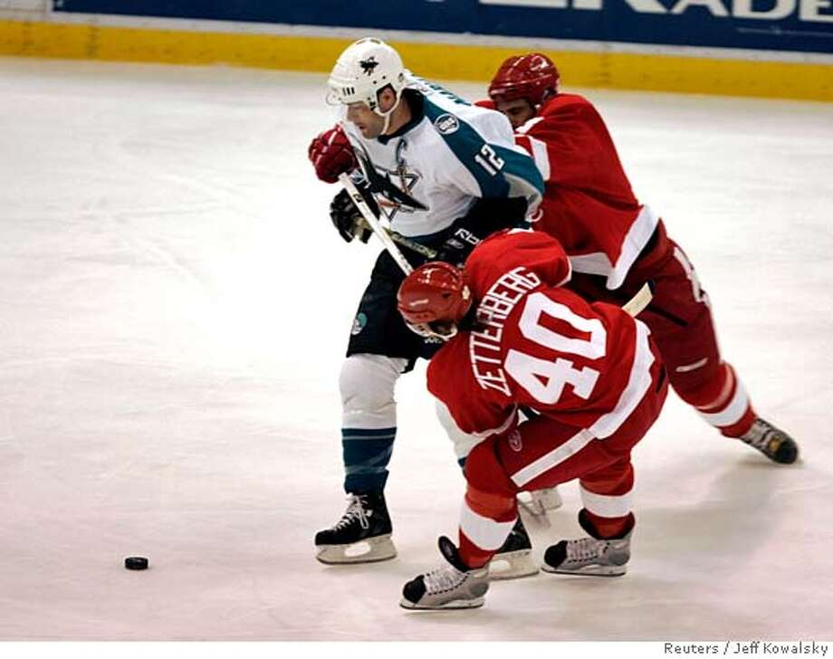 San Jose Sharks Patrick Marleau (12) is defended by Henrik Zetterberg (40) and Andreas Lilja of the Detroit Red Wings during the first period of Game 5 of their NHL Western Conference semi-finals hockey match in Detroit, Michigan May 5, 2007. REUTERS/Jeff Kowalsky (UNITED STATES) Photo: JEFF KOWALSKY