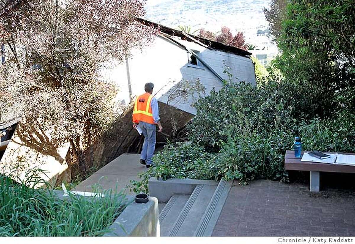 SHOWN: A building inspector walks down the side of the small house at 149 Mangels St. in San Francisco that fell down the hillside lot it is built on, and collapsed and twisted during that fall. Demian Bulwa is the reporter for Metro. These pictures were made in San Francisco, CA. on Sunday, May 6, 2007. (Katy Raddatz/The Chronicle) **