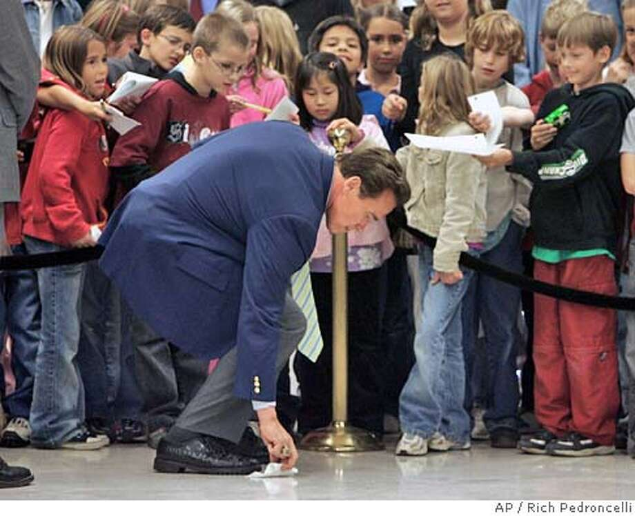 Gov. Arnold Schwarzenegger picks up a piece of paper dropped by one the children waiting for his autograph, as he returned to his office after holding a news conference at the Capitol in Sacramento, Calif., Thursday, Nov. 10, 2005. Schwarzenegger met with the press for the first time since his ballot intiatives were rejected by voters in Tuesday's special election saying, that he needed to learn more patience in seeking government reform. (AP Photo/Rich Pedroncelli) Photo: RICH PEDRONCELLI