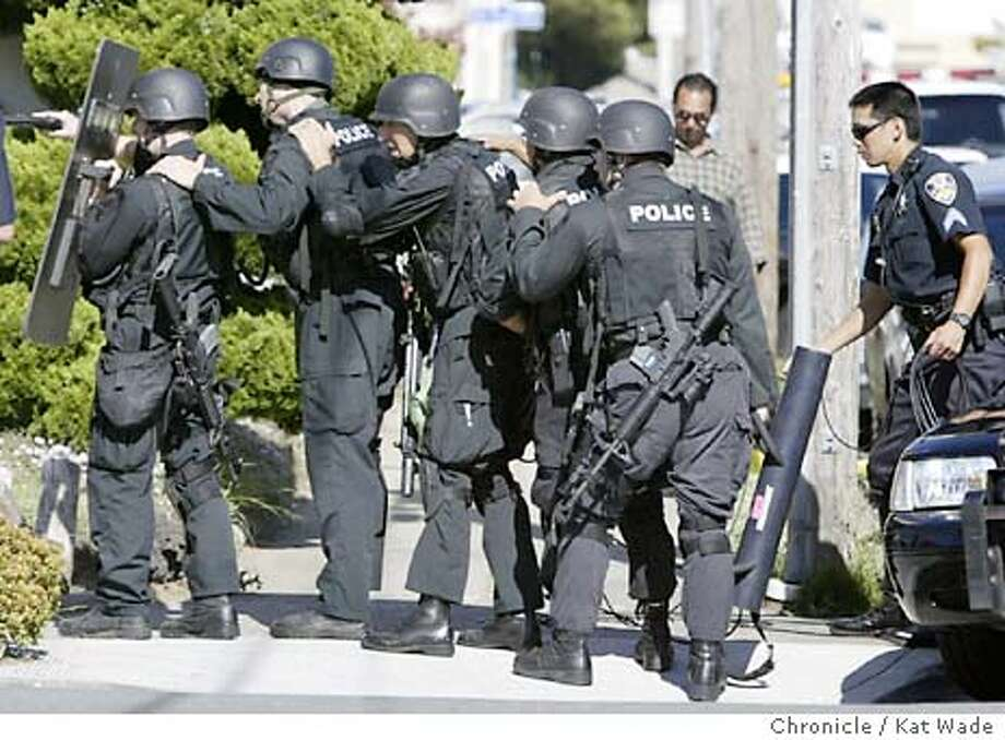 San Francisco's S.W.A.T. team prepares to charge the home where the man that first shot a mother and child and then stabbed two San Francisco police officers is held up in his home on Woodrow Street in Daly City on 8/11/03 in San Francisco. KAT WADE / The Chronicle Photo: KAT WADE