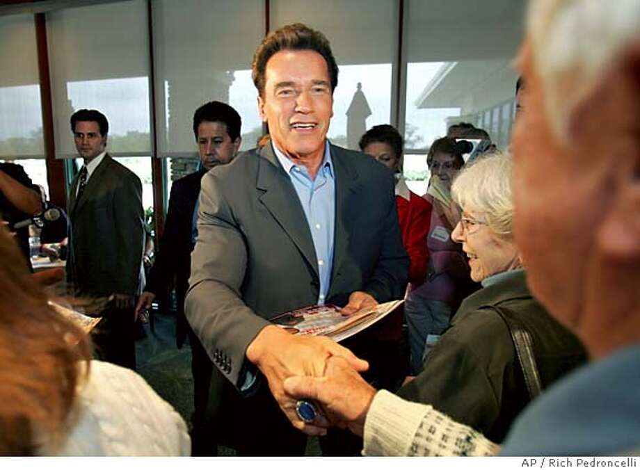 Gov. Arnold Schwarzenegger shakes hands with Eric Nicholls, right, while handing out campaign literature for his ballot measures while visiting the Sun City retirement community in Roseville, Calif., Monday, Nov. 7, 2005. With one day left before the special election, Schwarzenegger was traveling about the state to urge voters to get out and vote for his intiatives.(AP Photo/Rich Pedroncelli) Photo: RICH PEDRONCELLI