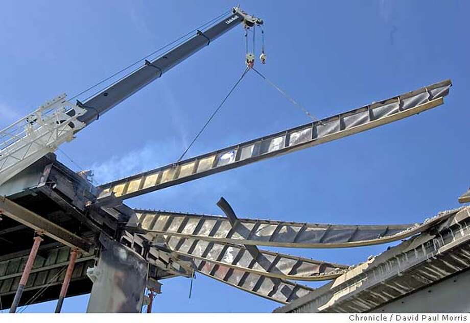 EMERYVILLE, CA - APRIL 30: A worker cuts on one of the steel beams as they prepare to remove it from the freeway overpass on April 30, 2007 in Emeryville, California. A tanker truck crashed and burned causing the elevated roadway that carried eastbound traffic from the Bay Bridge onto Interstates 580 and 980 and state Highway 24 to melt and crumble to the ground. (Photo by David Paul Morris/The Chronicle) Photo: David Paul Morris