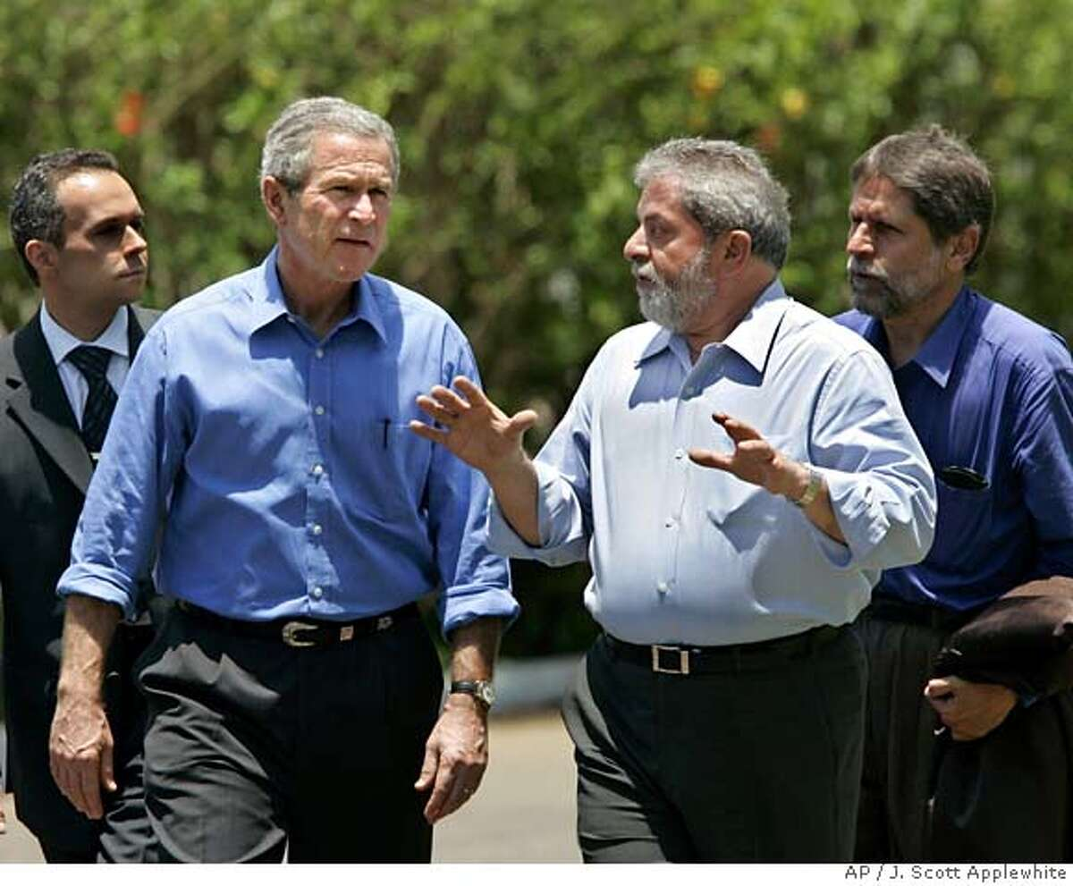 President Bush and Brazil's President Luiz Inacio Lula da Silva, right, confer through interpreters as they walk at his country retreat, Granja do Torto, outside of Brasilia, Sunday, Nov. 6, 2005. A day after the end of the Summit of the Americas, in Mar del Plata, Argentina, President Bush acknowledged that he has more work to do to persuade Brazil of the value of a vast proposed free-trade zone for the Western Hemisphere. (AP Photo/J. Scott Applewhite) EFE OUT