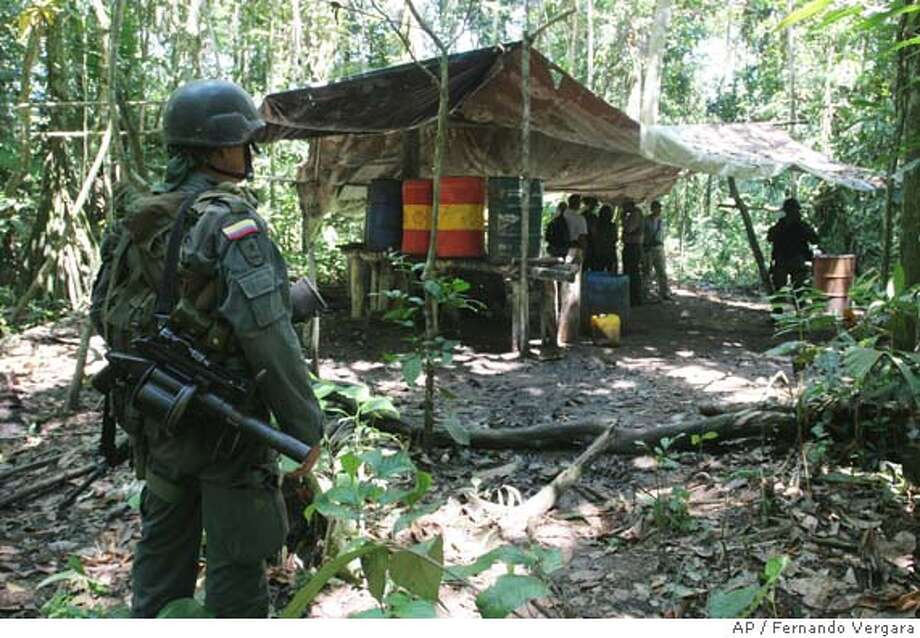 An anti-narcotic police stands guard in a drug lab in the village of Puerto Arturo near the Sierra Macarena National Park on August 26, 2005. Sierra Macarena is most threatened by cocaine. A recent flight over part of its 1.6 million acres revealed a trail of ugly gashes and charred trunks of trees felled by coca planters. The intruders also have built dozens of makeshift drug labs in the park and in the nearby village of Puerto Arturo, bringing in tons of gasoline, cement, hydrochloric acid and other toxic chemicals to process the coca leaves into cocaine. All of it pollutes the rivers and soil. (AP Photo/Fernando Vergara) Ran on: 10-02-2005  A police officer stands guard at a drug lab in the village of Puerto Arturo, near Sierra Macarena National Park. Ran on: 11-06-2005  An anti-narcotics officer guards a drug lab in the village of Puerto Arturo, near the Sierra Macarena National Park in Colombia. Ran on: 11-06-2005  An anti-narcotics officer guards a drug lab in the village of Puerto Arturo, near the Sierra Macarena National Park in Colombia. Photo: FERNANDO VERGARA