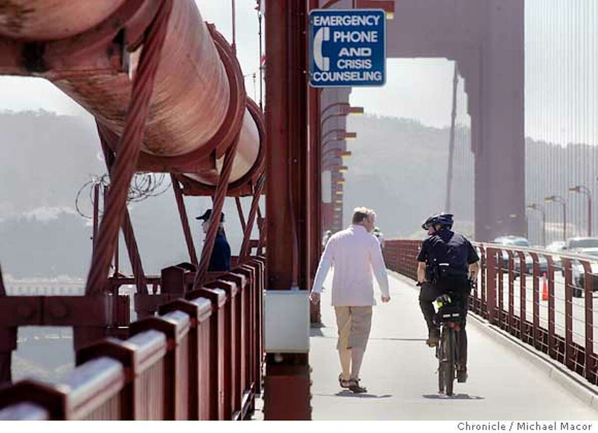 10/5/05 12:40:06 PM Officer Carman talks with pedestrians as he patrols the span. CHP Officer John Carman patrols the Golden Gate Bridge on his bicycle. Suicide story about the CHP and Golden Gate Bridge District patrol officers who try to stop people from jumping off the bridge. 10/5/05 in San Francisco Ca Michael Macor / San Francisco Chronicle