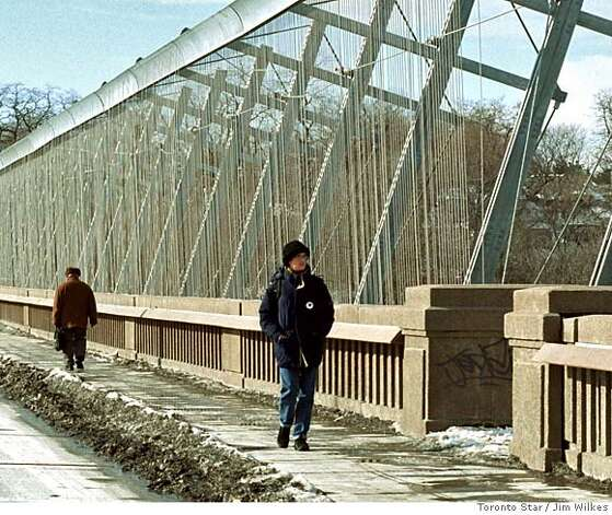 The Bloor Street bridge in Toronto on January 15, 2003. Pedestrians walking along the sidewalk after the suicide barrier was installed. It is made up of a series of cables.  Photo by Jim Wilkes/Toronto Star