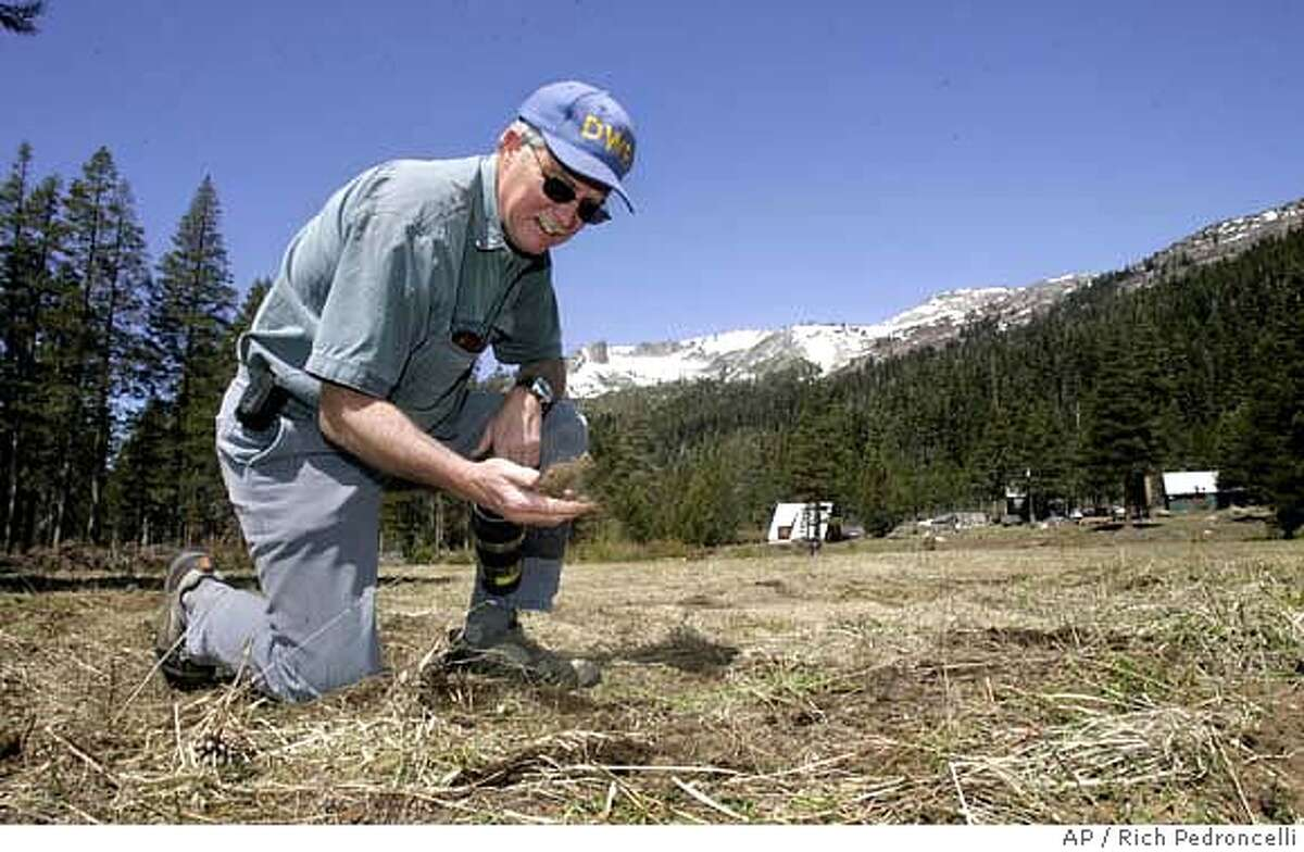 Hydrologist Frank Gehrke sifts a handful of dirt in a field that he normally takes a snow pack reading for the Department of Water Resources snow survey near Echo Summit, Calif., Tuesday, May 1, 2007. Results of the snow survey's, held in four different locations, show the snow pack, state wide, to be only 29 percent of normal for the season. (AP Photo/Rich Pedroncelli)
