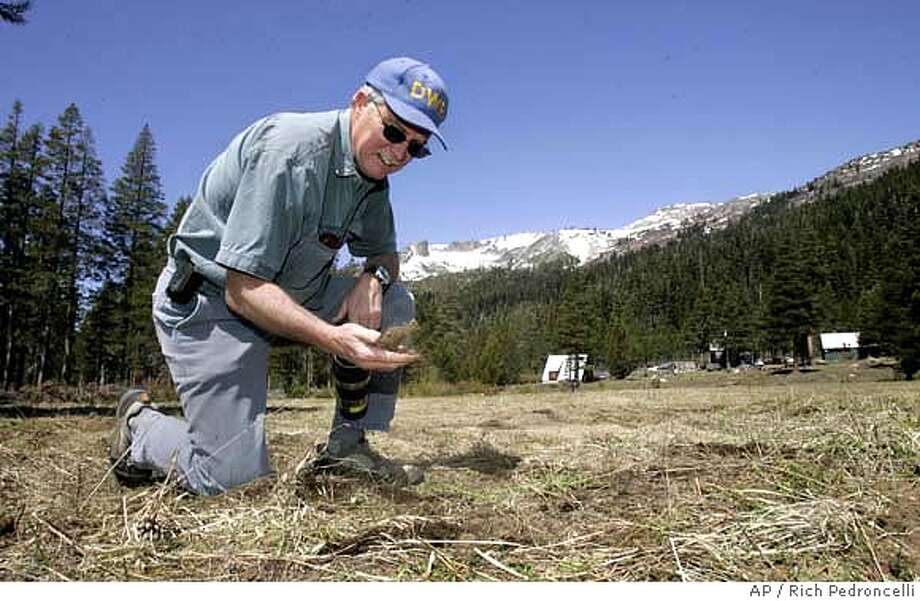 Hydrologist Frank Gehrke sifts a handful of dirt in a field that he normally takes a snow pack reading for the Department of Water Resources snow survey near Echo Summit, Calif., Tuesday, May 1, 2007. Results of the snow survey's, held in four different locations, show the snow pack, state wide, to be only 29 percent of normal for the season. (AP Photo/Rich Pedroncelli) Photo: Rich Pedroncelli