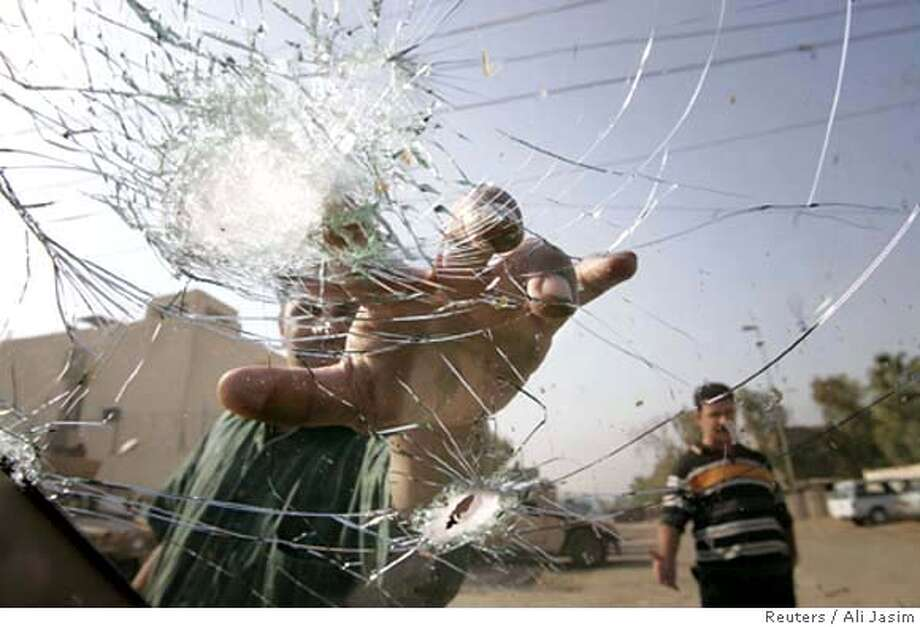 An Iraqi man touches a bullet hole in the windscreen of a car used by Ghalib Abdul Madhi, an advisor to the Iraqi cabinet, in Baghdad October 30, 2005. Madhi escaped death when gunmen attacked him in Baghdad, police said. He was wounded and his driver was killed. REUTERS/Ali Jasim 0 Photo: ALI JASIM