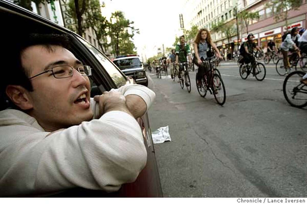 CRITICALMASS_25988.JPG Shoru Hatamov from San Francisco parked his car on Market Street to enjoy the 15-minute parade of bikes Friday night. He went on to say