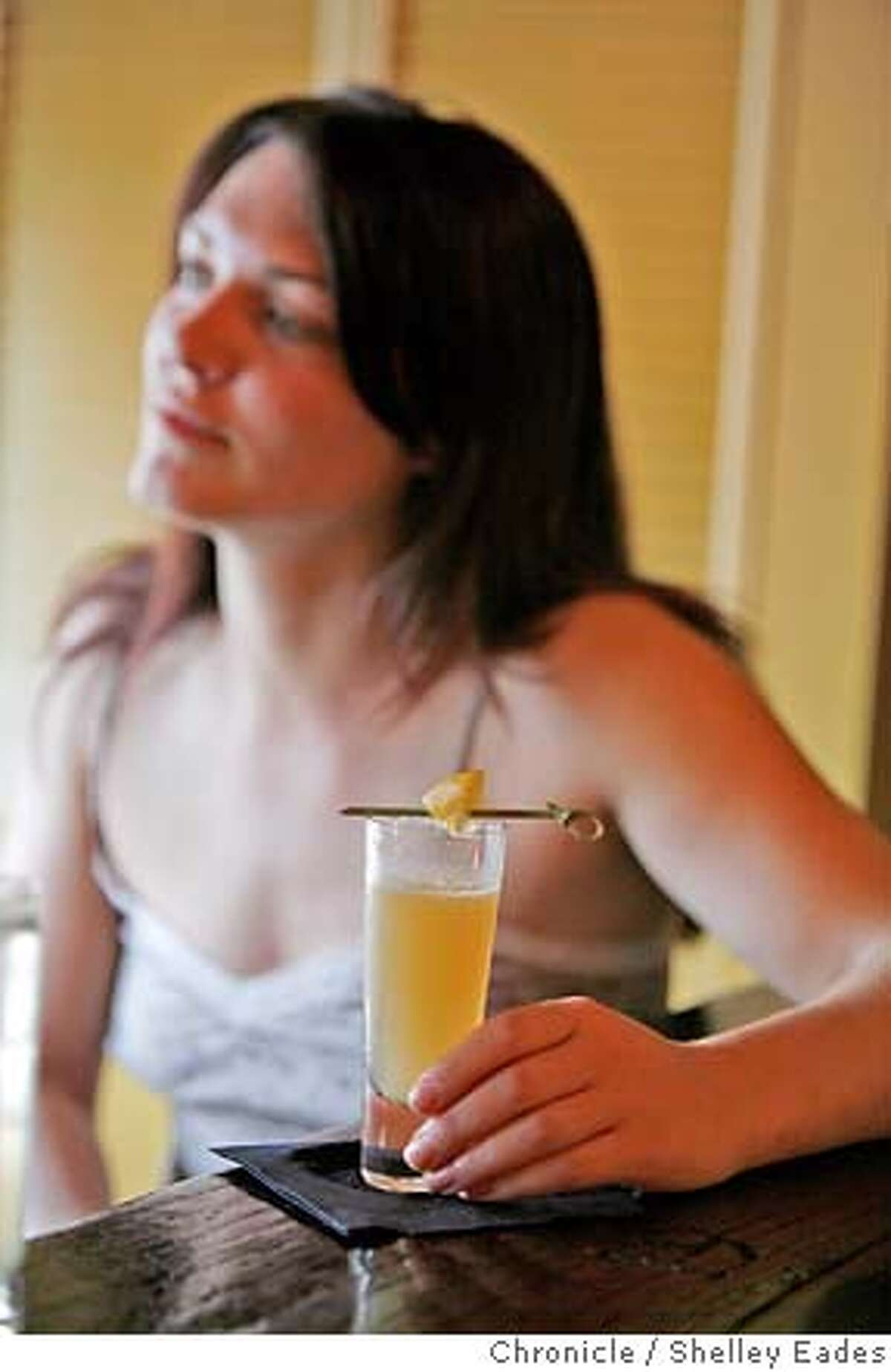 Jill Smagula enjoys a Mellow Yellow cocktail prepared by Hyatt at the Alembic. Chronicle photo by Shelley Eades