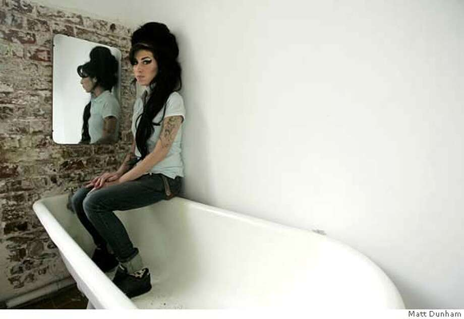 PHOTO GOES WITH SXSWSIDE17 British singer Amy Winehouse poses for photographs after being interviewed by the Associated Press at a studio in north London, Friday Feb. 16, 2007. Winehouse is not your average suburban London girl. First off, there's the diminutive singer's larger-than-life look - black beehive of hair, mascara-drenched eyes, old-school sailor tattoos. It's part Dusty Springfield, part Morticia Addams. Then, there's the 23-year-old's extraordinary voice, like Billie Holiday channeling the Shangri-Las. (AP Photo/Matt Dunham)  Ran on: 03-17-2007  Amy Winehouse performed songs from her new album, &quo;Back to Black,&quo; on Thursday at the South by Southwest music festival. Photo: MATT DUNHAM