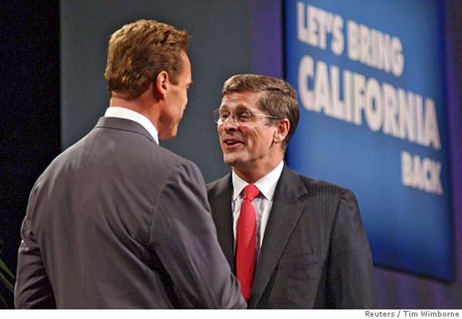 California gubernatorial candidate Arnold Schwarzenegger (L) greets former candidate Bill Simon on stage at the Memorial Auditorium in Sacramento on October 1, 2003. Former Republican candidate Simon, who pulled out of the October 7 recall election race some weeks ago, today showed his support for Schwarzenegger by introducing him at an event where the actor outlined some of the initial actions he would take if he is elected as California governor. REUTERS/Tim Wimborne CAT 3-col 1-line caption Photo: TIM WIMBORNE