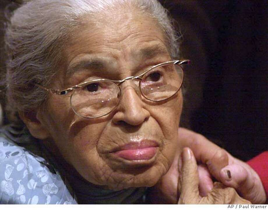 ** FILE ** Civil rights pioneer Rosa Parks holds the hand of a well-wisher at a ceremony honoring the 46th anniversary of her arrest for civil disobedience Saturday, Dec. 1, 2001, at the Henry Ford Museum in Dearborn, Mich. Parks, whose refusal to give up her bus seat to a white man sparked the modern civil rights movement, died Monday Oct. 24, 2005. She was 92. (AP Photo/Paul Warner) Photo: PAUL WARNER