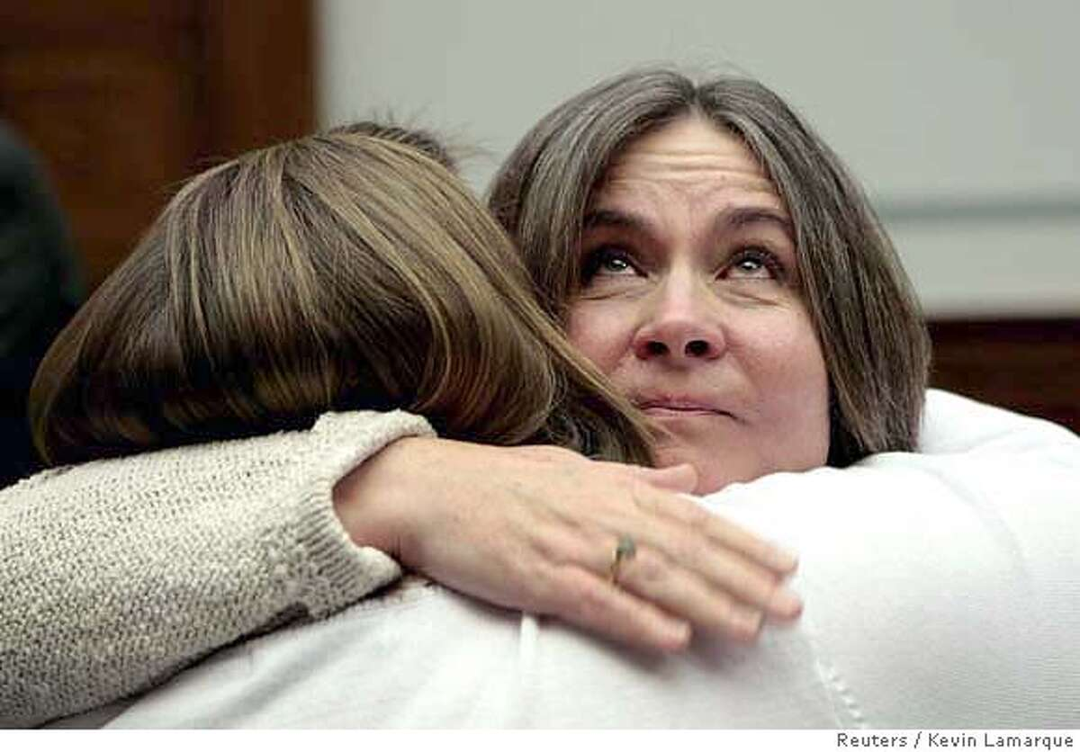 Mary Tillman, mother of former football star Pat Tillman, looks up as she receives a hug after testifying about Pat Tillman's death in battle at a hearing titled