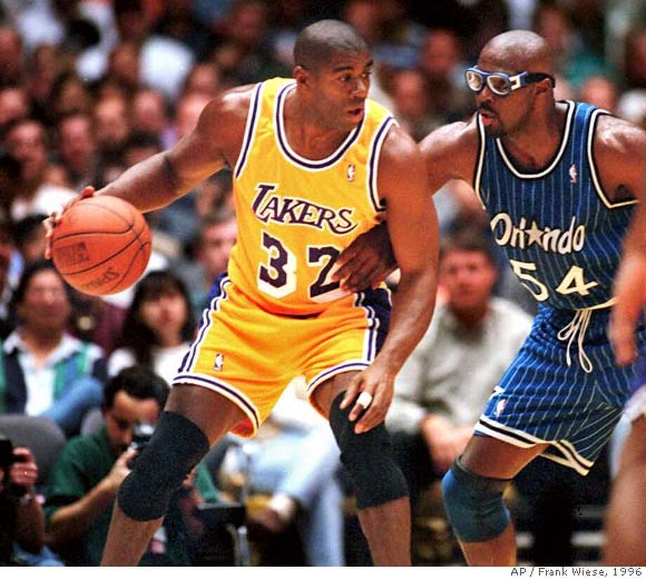 """FILE--Los Angeles Lakers' Earvin """"Magic"""" Johnson (32) looks for a passing possibility while Orlando Magic's Horace Grant (54) defends during their game at the Forum in Inglewood, Calif., Sunday, March 17, 1996. Johnson, whose comeback after a 4 1/2 year absence began in triumph and ended in controversy, called it quits again Tuesday May 14, 1996, saying it was time to return to his business interests. (AP Photo/Frank Wiese) Photo: FRANK WIESE"""