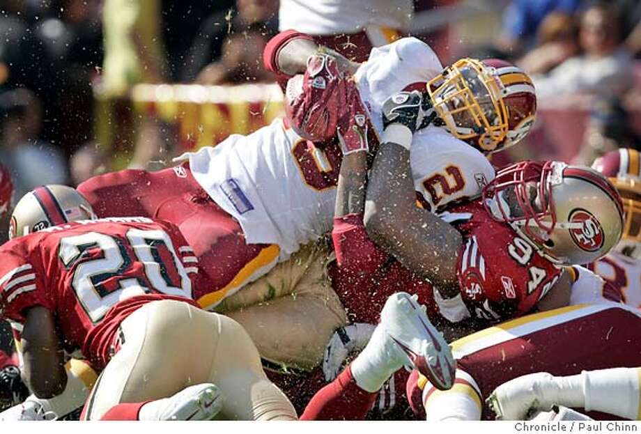 Washington's Clinton Portis kicks up some turf as he's wrestled to the ground by Marques Douglas (94) in the first quarter of the San Francisco 49ers vs. Washington Redskins game at Fedex Field on 10/23/05 in Landover, Md. The Redskins beat the 49ers 52-17.  PAUL CHINN/The Chronicle Photo: PAUL CHINN