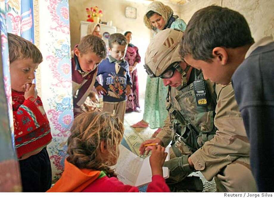 U.S. army Lieutenant Andrew Fleming teaches children numbers during a routine visit to a family in Tikrit, Iraq October 22, 2005. The Independent Electoral Commission of Iraq said on Saturday it had found no instances of serious fraud in an October 15 constitutional referendum and it was still verifying some results only because of statistical issues. REUTERS/Jorge Silva 0 Photo: JORGE SILVA