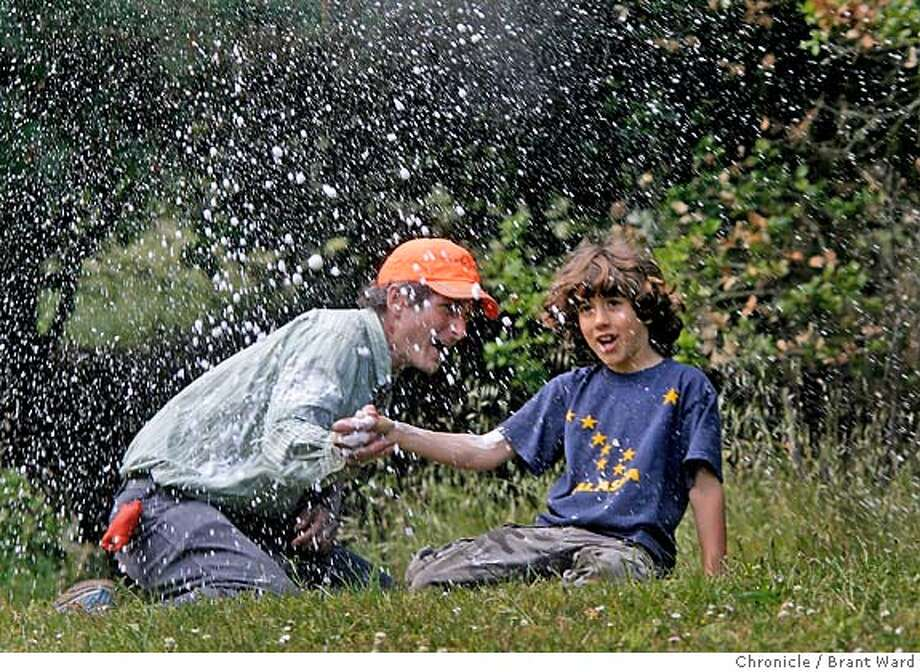 earthday100.JPG  It's snowing vinegar and baking soda as Samir Sadrane, right, seven years, and Chris Giorni, left, the founder of TreeFrogTreks.com, sit beneath the exhaust of a plastic bottle shot into the air by the chemical reaction.  McLaren Park, San Francisco's second largest park, hosted an earth day celebration Sunday. Many local residents attended the event which featured a chance to learn about nature from local activists. McLaren Park is often forgotten, but it has many trails, dog-friendly parks and the ever-popular Jerry Garcia Amphitheater where the event was held.  {Brant Ward/San Francisco Chronicle}4/22/07 Photo: Brant Ward