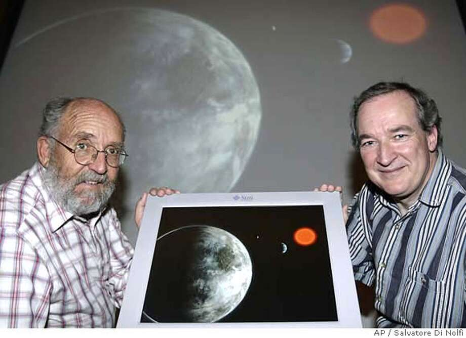Swiss astrophysicist and director of the Geneva Observatory, Michel Mayor, left, and Swiss astrophysicist Stephane Udry, right, hold an artist rendering on Tuesday, April 24, 2007 showing the planetary system around the red dwarf Gliese 581. Mayor and Udry have discovered a planet outside our solar system that is potentially as habitable as Earth, at left, with similar temperatures, they announced. (AP Photo/Keystone, Salvatore Di Nolfi) EMBARGOED FOR USE UNTIL 2300GMT TUESDAY APRIL 24TH 2007 Photo: SALVATORE DI NOLFI