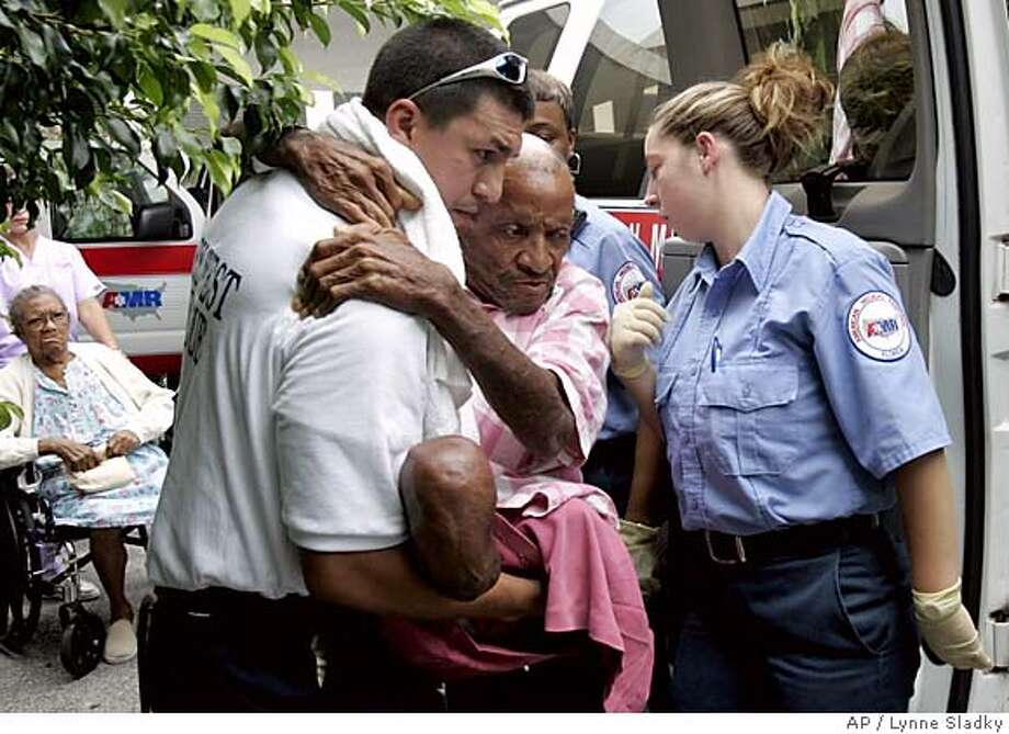 Juan Saavedra, a paramedic from Broward County, Fla.., left, loads Dave Green, center, into an ambulance at the Key West Convalescent Center on Stock Island in Key West, Fla. Sunday, Oct. 23, 2005. The center is evacuating patients as part of the mandatory evacuation in effect in the Florida Keys as Hurricane Wilma is expected to make landfall early Monday. At right is paramedic Kristina Landis. (AP Photo/Lynne Sladky) Photo: LYNNE SLADKY
