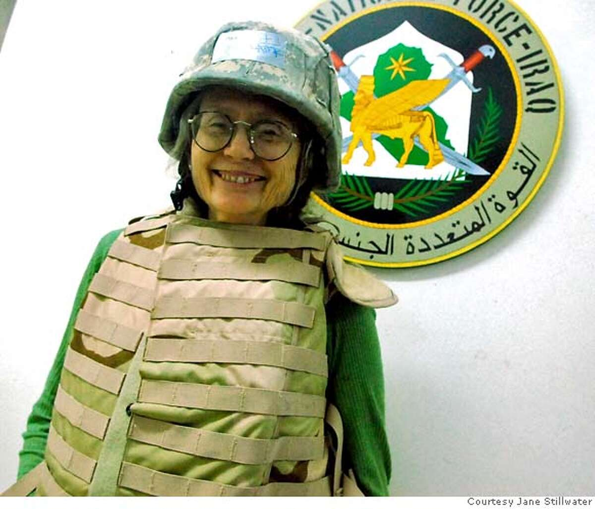 While in Iraq, blogger Jane Stillwater poses in front of an emblem of the Multi-National Forces of Iraq in a photograph that she sent home to friends and supporters in the United States. PHOTO COURTESY JANE STILLWATER.
