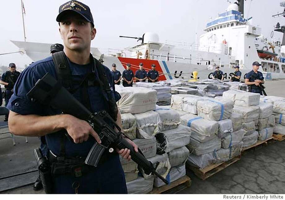 United States Coast Guards stand by 11.5 tons of cocaine in Alameda, California October 21, 2005. The Coast Guard seized the 11.5 tons of cocaine, with a street value of approximately $750 million, in three drug interdictions along the coast of South America. The Coast Guard has seized approximately 150 tons of cocaine in total for their 2005 fiscal year. REUTERS/Kimberly White Photo: KIMBERLY WHITE