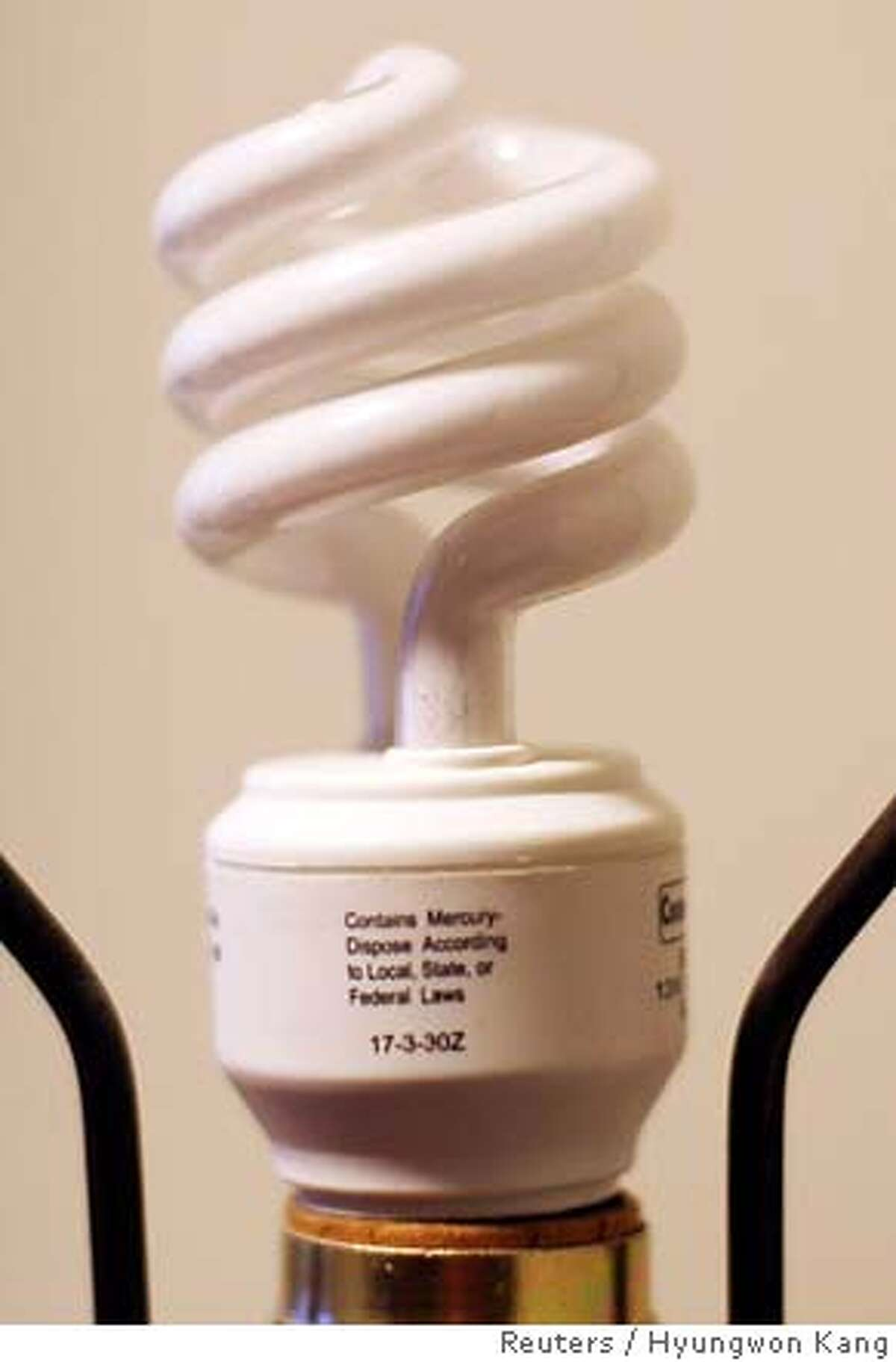 A compact fluorescent light bulb which has mercury warning on it, is pictured in Great Falls March 28, 2007. Mercury is poisonous, but it's also a necessary part of most CFLs, the kind that environmentalists and some governments are pushing as a way to cut energy use. To prevent mercury from getting into landfills, the U.S. Environment Protection Agency, CFL makers and various organizations advocate recycling. To match feature ENVIRONMENT-LIGHTBULBS/ REUTERS/Hyungwon Kang (UNITED STATES) 0