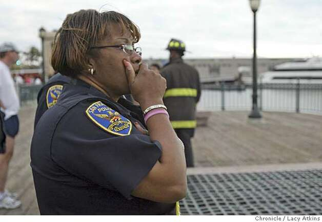 Event on 10/19/05 in San Francisco.  SFPD officer Debra Anderson (name to be confirmed) watches as rescuers searched Wednesday night for the bodies of at least two young children who were reportedly tossed in San Francisco Bay near Pier 7, a popular waterfront stretch, according to Fire Chief Joanne Hayes-White. Coast Guard boats and a helicopter searched the waters as police officers and firefighters investigated from the shore. Hayes-White reported that a witness called 911 to report that two, and possibly three children, were dropped from Pier 7 into the water.  Lacy Atkins / The Chronicle Photo: Lacy Atkins