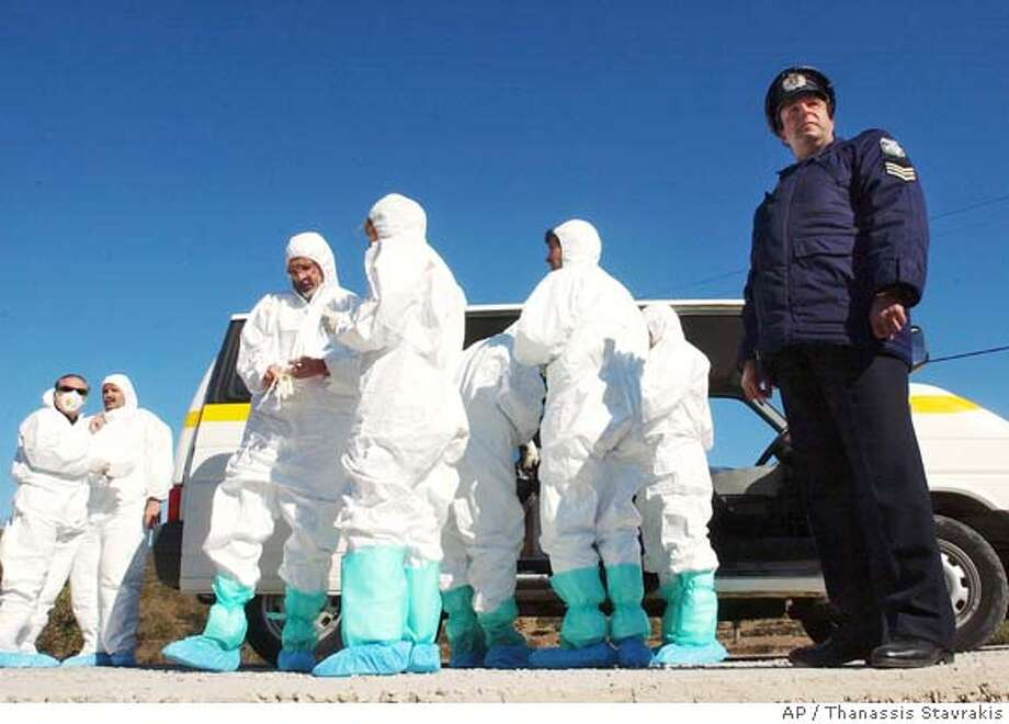 Inspectors from the EU's Food and veterinary Office and Greek colleagues wear protective clothing as a policeman looks on, outside a farm where a sick turkey was found on Monday, on the tiny Aegean Sea island of Oinouses, Greece, on Thursday, Oct. 20, 2005. Oinouses residents expressed relief that a preliminary test for bird flu found no evidence of the virus on the farm where a sick turkey was found. (AP Photo/Thanassis Stavrakis) Photo: THANASSIS STAVRAKIS