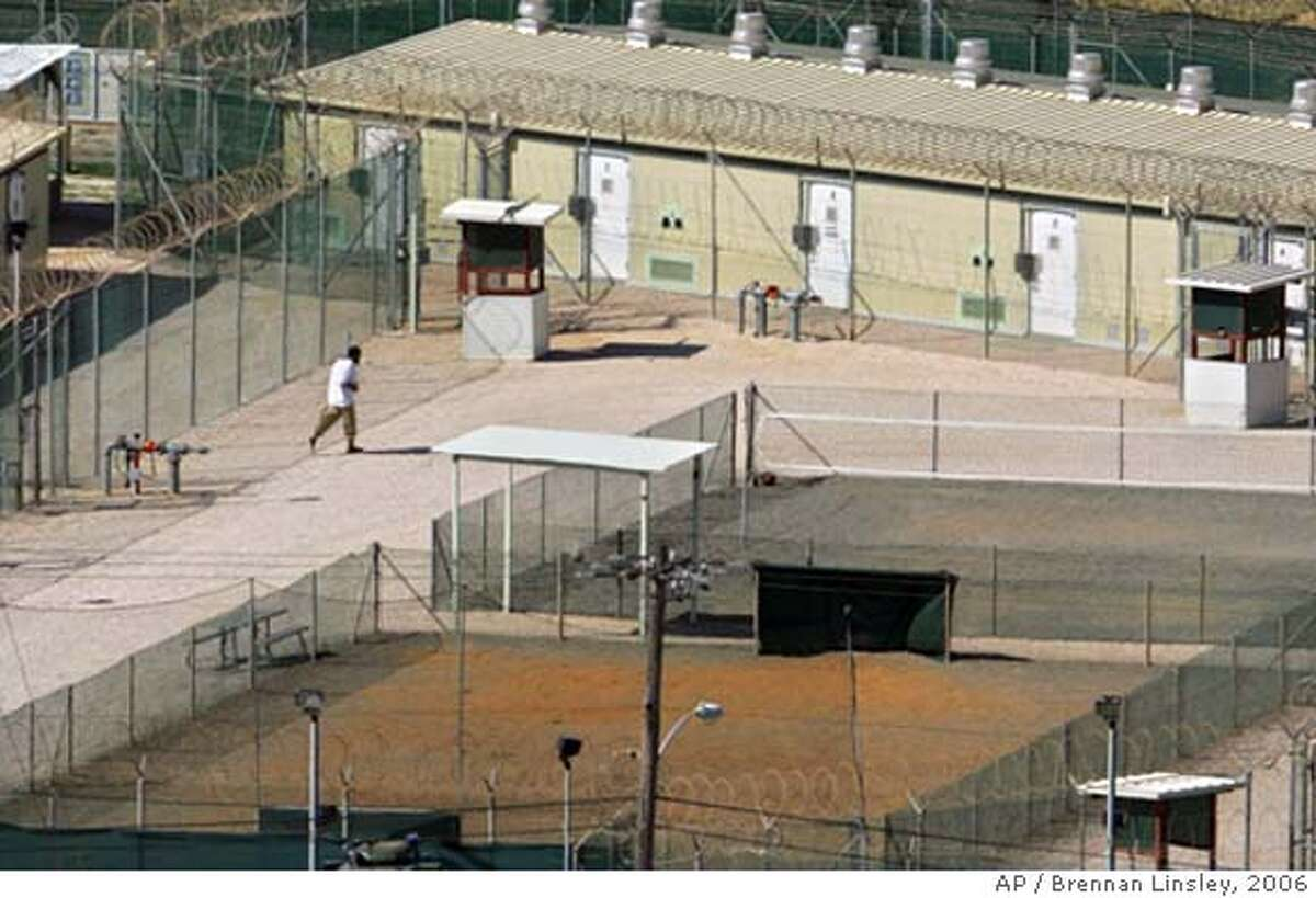 ** FILE ** A detainee jogs around the exercise area at the medium security portion of the detention facility at the Guantanamo Bay U.S. Naval Base, Cuba, in this Sept. 21, 2006 file photo. David Hicks, an Australian held at Guantanamo for five years, pled guilty earlier in the week and was found guilty Friday of providing material support for terrorism, marking the first conviction at a U.S. war-crimes trial since World War II. (AP Photo/Brennan Linsley)