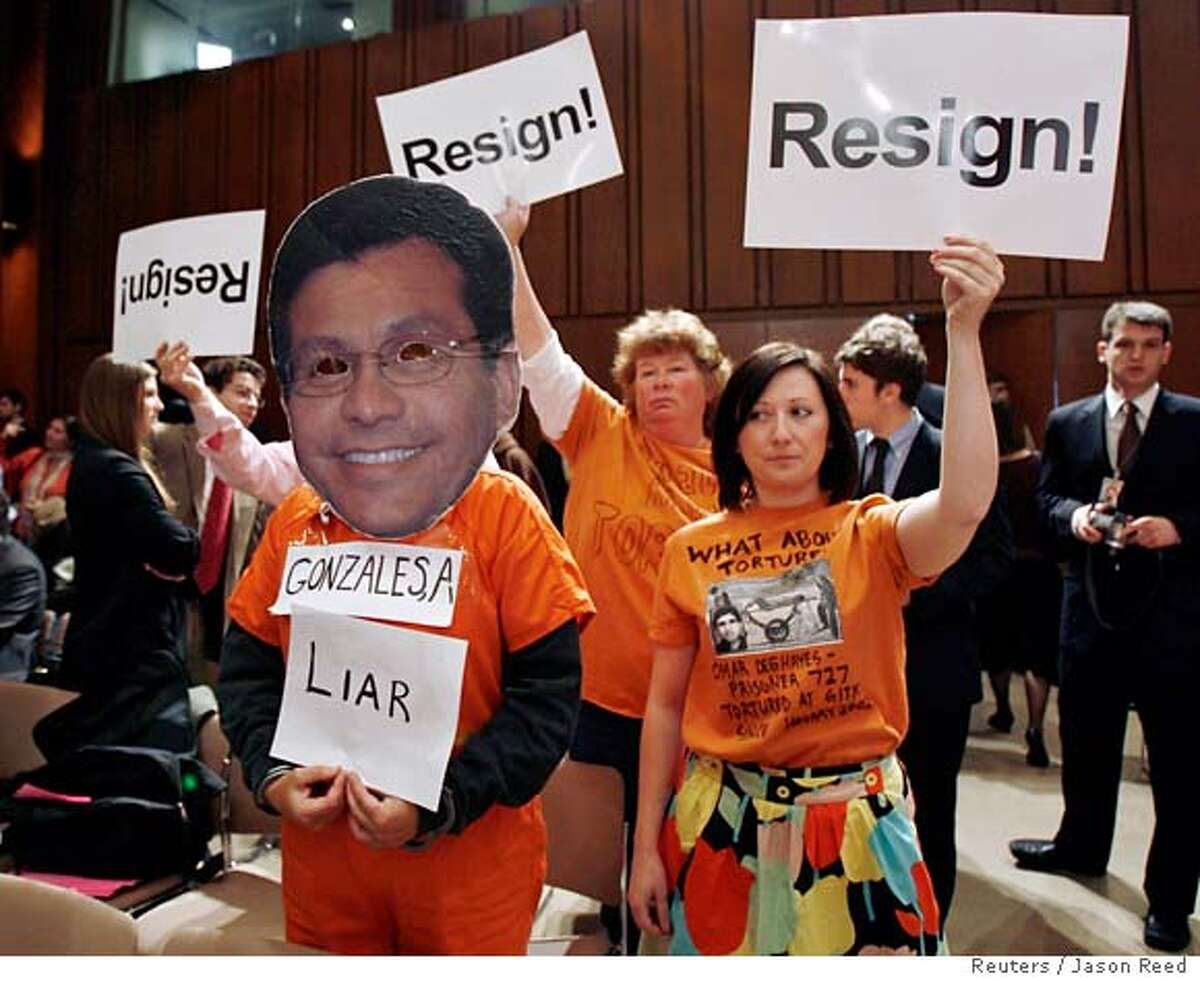 Protesters, including one wearing a mask of U.S. Attorney General Alberto Gonzales (L), call for Gonzales' resignation during a Senate Judiciary Committee hearing on Capitol Hill in Washington, April 19, 2007. Gonzales, facing bipartisan calls to resign, is making a possible make-or-break appearance before the congressional panel investigating the firing of the U.S. attorneys. REUTERS/Jason Reed (UNITED STATES) 0