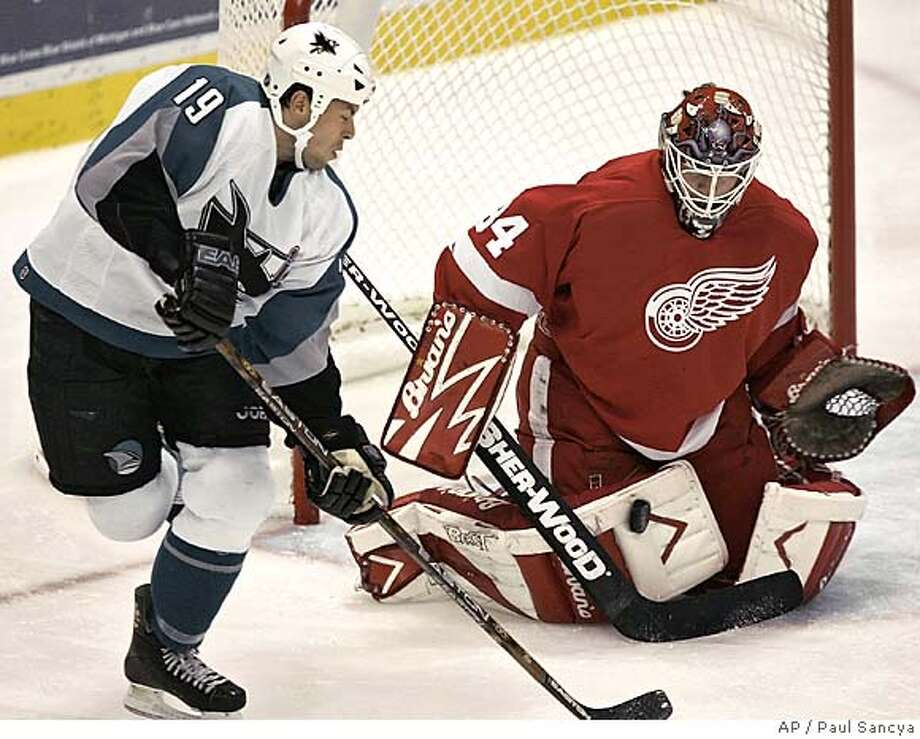 Detroit Red Wings goalie Manny Legace, right, stops shot by San Jose Sharks' Marco Sturm of Germany in the second period Monday, Oct. 17, 2005, in Detroit. (AP Photo/Paul Sancya) Photo: PAUL SANCYA