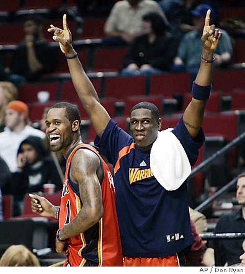 Golden State Warriors' Stephen Jackson, left, and Mickael Pietrus, of France, celebrate after the Warriors defeated the Portland Trail Blazers 120-98 on Wednesday, April 18, 2007, in Portland, Ore., clinching an NBA basketball playoff berth for the first time since 1994. Jackson led the Warriors with 31 points. (AP Photo/Don Ryan) Photo: Don Ryan