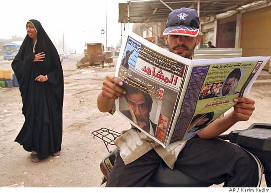 An Iraqi man reads a paper carrying a picture of ousted Iraqi leader Saddam Hussein on its front page in Baghdad, Iraq, Monday Oct. 17, 2005. Saddam Hussein's trial will start on Oct. 19, 2005.(AP Photo/Karim Kadim) Photo: KARIM KADIM