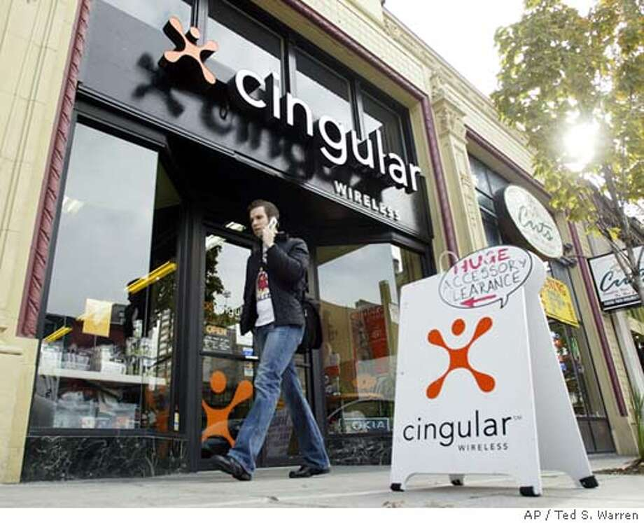A pedestrian talks on his phone as he walks past a Cingular Wireless store in Seattle's University District Monday, Oct. 25, 2004. Cingular Wireless LLC has moved one step closer to finalizing its $41 billion acquisition of AT&T Wireless Services Inc. and creating the nation's largest cell phone company after the Justice Department on Monday approved the deal. (AP Photo/Ted S. Warren) Ran on: 10-26-2004  In Seattle's University District, a pedestrian talks on his cell phone passing a Cingular Wireless store. Ran on: 05-30-2005  Verizon and Cingular are beefing up their prepaid options, to snare customers (children, the elderly) who don't have credit. Photo: TED S. WARREN