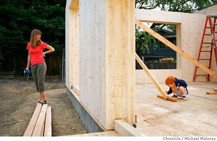 The 12 inch thick walls are made of multiple pieces of European larch held together by wood dowels to provide superior insulation. Soon to be homeowner Shannon Neve (left) watches as her 2 year old son Caleb Neve plays in their living area still under construction.  Pure Wood Solutions is using a home construction process used throughout Germany, Austria and Scandinavia to build it's first house in Walnut Creek, California. The factory automated process uses walls, ceilings and roofs made of 100% wood from sustainable and managed forests and without the use of glues, chemicals or even nails.  Photo by Michael Maloney / San Francisco Chronicle ***Shannon Neve, Caleb Neve MANDATORY CREDIT FOR PHOTOG AND SF CHRONICLE/NO SALES-MAGS OUT Photo: Michael Maloney