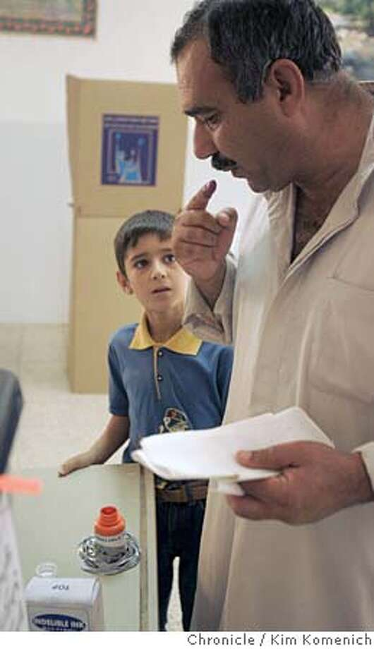 After voting, Saad Fathel Mohammed, 52 (right), blows on his finger to dry indelible ink as son Ali, 10, watches. Those who vote must get their finger stained.  We tour the Tikrit area as the Iraqi consititutional referendum takes place. Our story features two aspects of the referendum: the vote itself, at some of the 33 Tikrit area polling places, and then the backstory- the role of Lt. Col. Todd Wood and soldiers from the 2nd Battalion, 7th Infantry Regiment,1st Brigade of the Third Infantry Division, U.S. Army in making sure the Iraqi Army and Police are ready to support safe and secure elections without direct U.S. help.  San Francisco Chronicle Photo by Kim Komenich  10/15/05 Photo: Kim Komenich