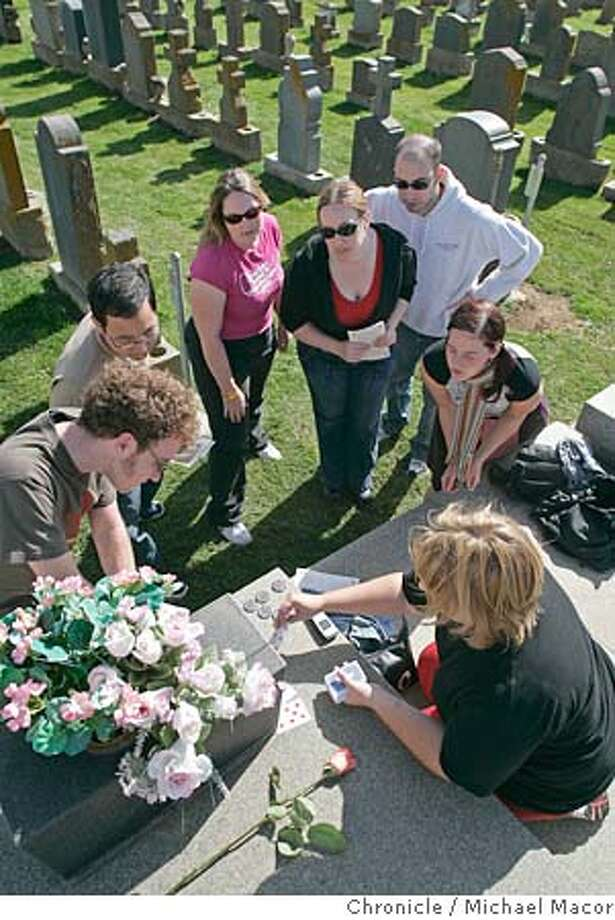 Suzi Blakley deals the next hand for her group, l to r- Sean Savage, Michael Li, Cathryn Gatcum, Michelle Heimburger, Huw Evans and Becky Uline. Graveyard Games will be in Colma, San Francisco's very own City of the Dead, so you can meet the living and play with the dead. Tombstone Hold �Em. Per the rules, we�ll arrive at the Italian Cemetery , find our host under the white arch holding a deck of cards. We�ll each bring a single flower to place on a grave to show some respect (and signal participation). We�ll start in by looking for poker chips left on tombstones, which we�ll need for the game, and finding the grave of someone we can prove died on our birthday. 10/15/05 in Colma, {state.} Michael Macor / San Francisco Chronicle Photo: Michael Macor