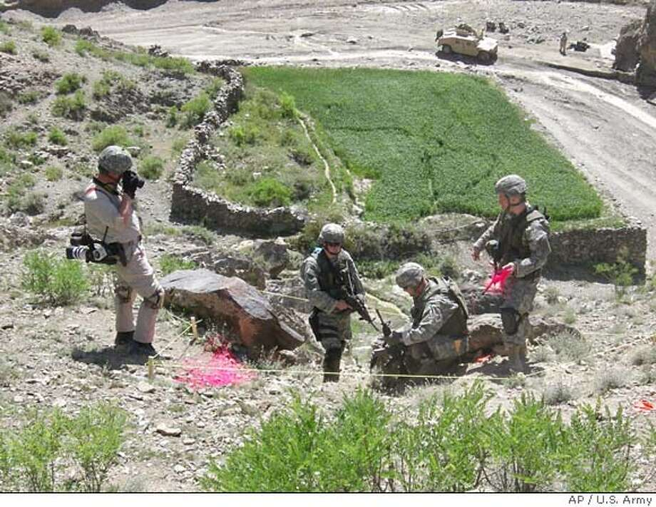 This April 2006 handout photo released by the United States Army Criminal Investigation Command in March 2007, shows a military re-enactment of the incident that took the life of Spc. Pat Tillman and wounded fellow Army Rangers Lt. David Uthlaut and Spc. Jade Lane on April 22, 2004 near the village of Manah in eastern Afghanistan. This frame shows investigators at the scene of Tillman's death, with a Humvee in the background to show the approximate area near where his fellow Rangers fired at him. The Army released these images recently as it announced the findings of investigations on the incident. (AP Photo/U.S. Army) Photo: U.S. Army